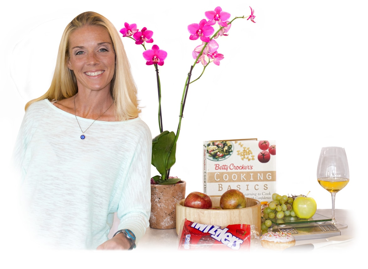 Dr. Tiff in an ocean blue top leaning on counter with items such as a doughnut, a cookbook, a bag of Twizzlers, grapes, apples, white wine, a food scale, and a potted orchid